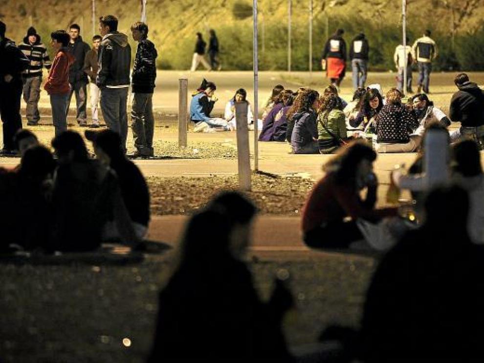Unos jóvenes, en el botellón que se organiza durante el Pilar en las puertas del recinto de Interpeñas.