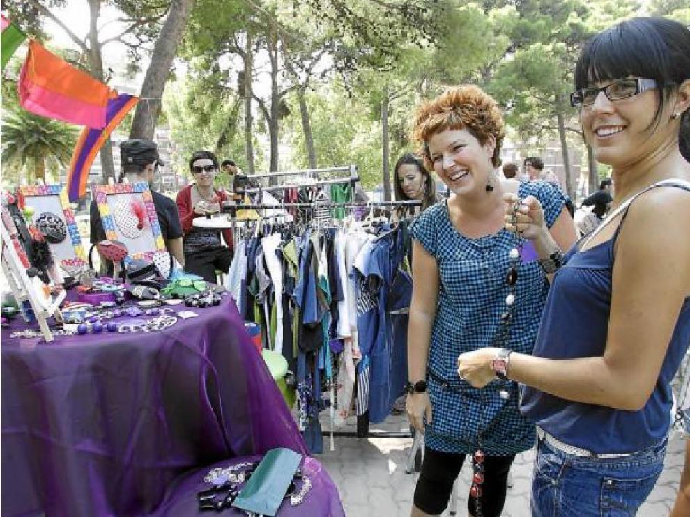 Vicky enseña algunas de sus creaciones a una cliente en el mercadillo del parque Palomar