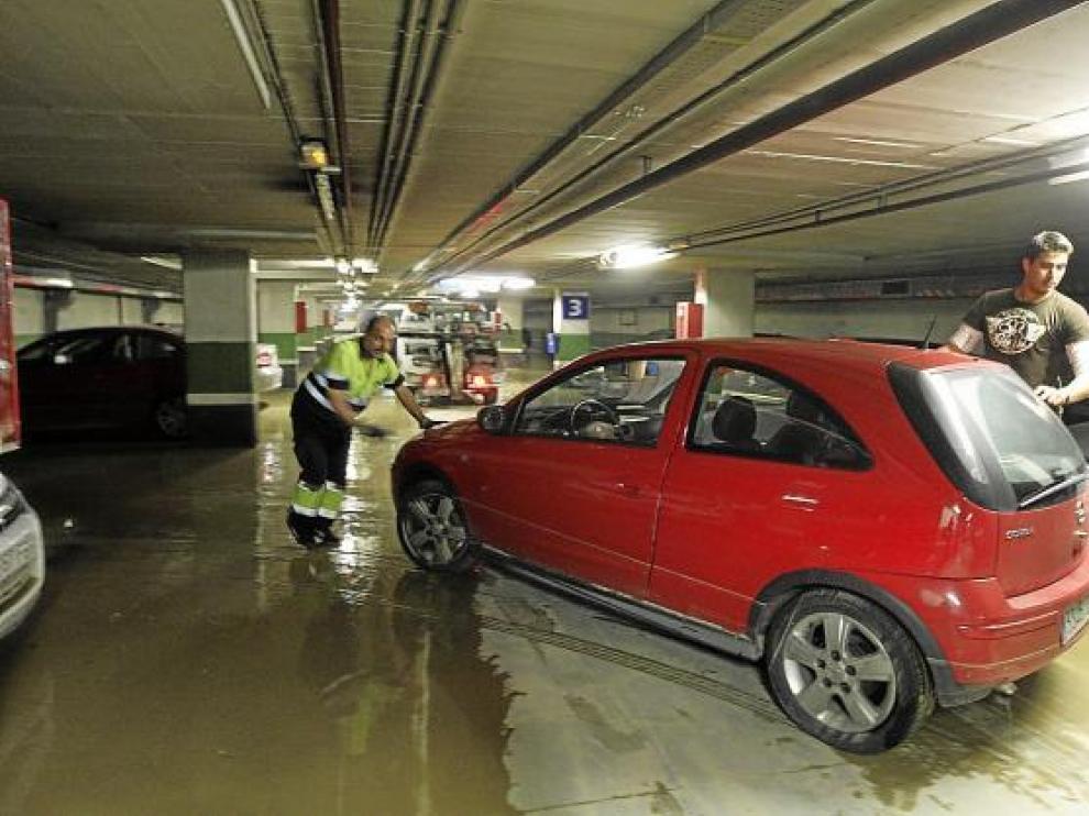 Una grúa retira del aparcamiento uno de los vehículos afectados por la inundación.