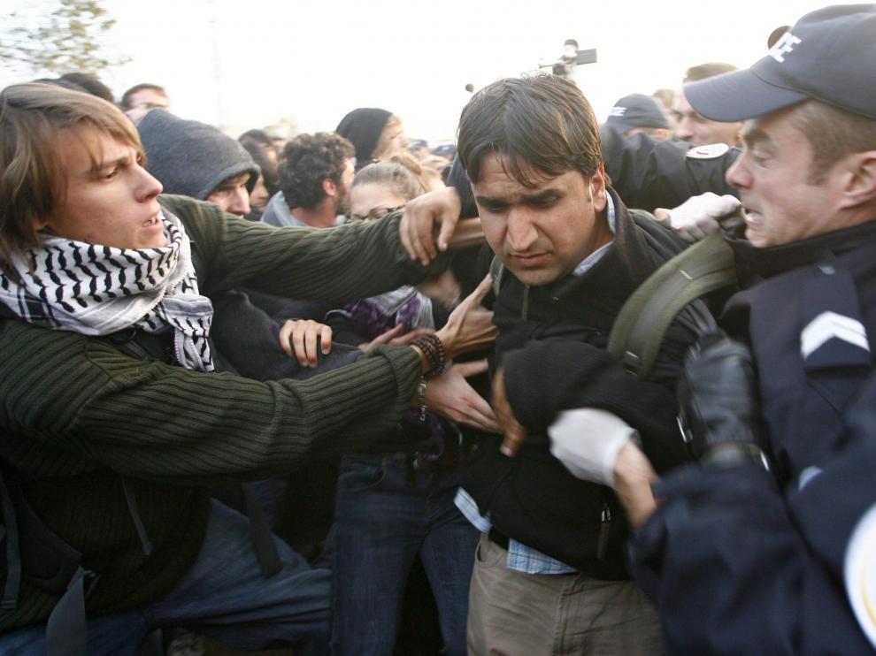 Policias detienen a un inmigrante ilegal durante la operación de desmantelamiento en un campamento de inmigrantes