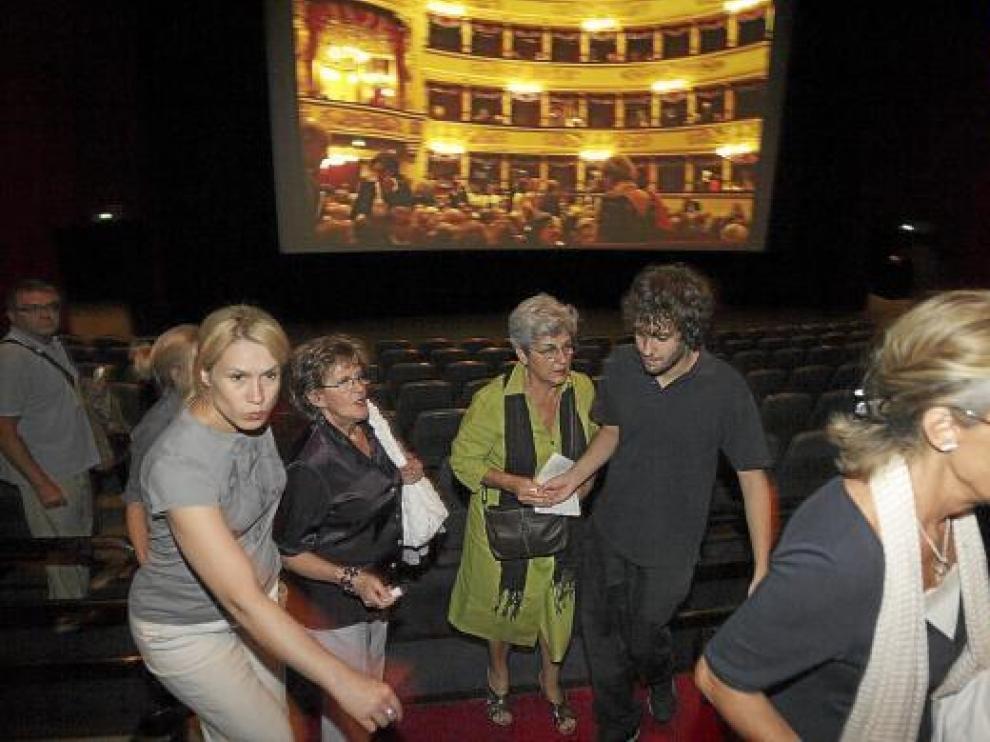 Varias personas buscando ayer asiento en los Cinesa Grancasa, con La Scala proyectada al fondo.