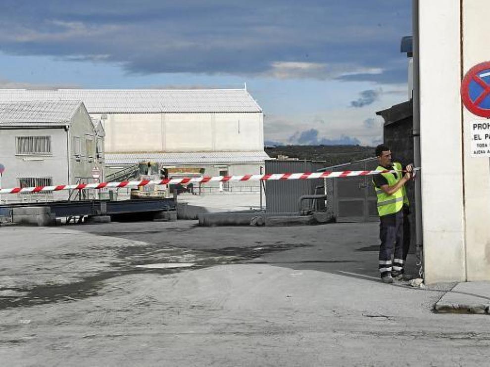 Tras el siniestro, un operario de Agrimartín tiende un cordón para cortar el paso al interior de la fábrica.