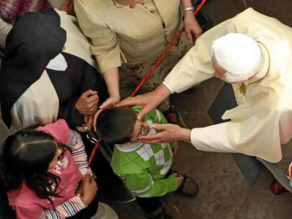 Benedicto XVI santigua a un niño en la iglesia de Nuestra Señora de la Victoria de Praga.