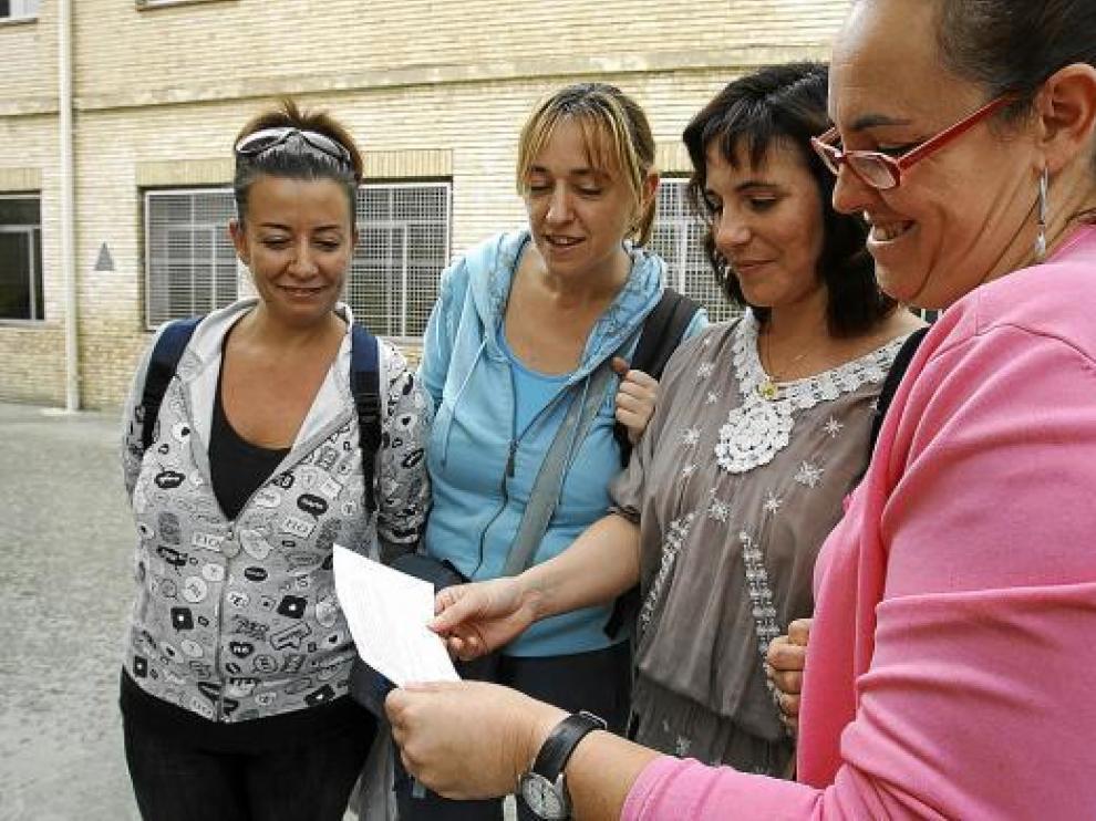 Madres del colegio Pío XII leen la encuesta que les ha dado el centro para recabar su opinión.