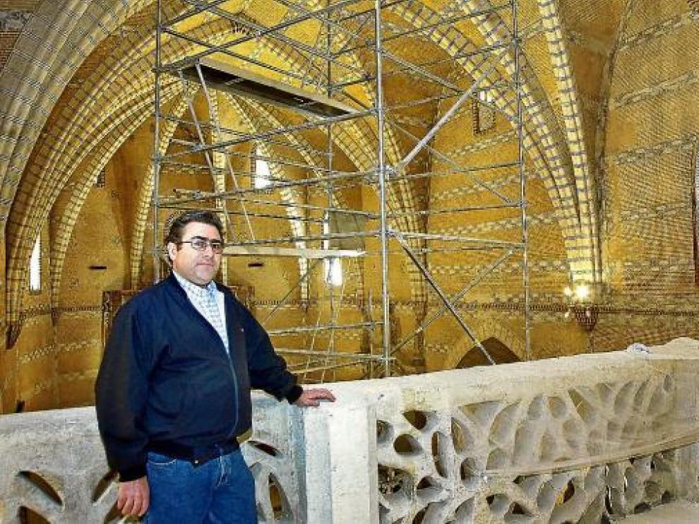 El párroco de la iglesia posa delante del andamio que sujeta el arco con problemas estructurales.