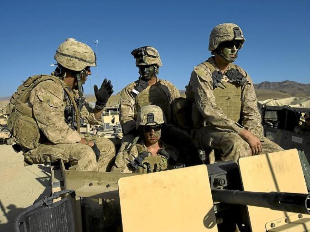 Marines estadounidenses, con pintura de camuflaje en sus caras, se preparan para salir de su base en Farah, ayer en Afganistán.