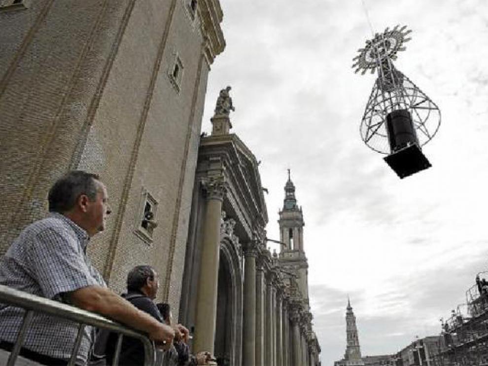 Varios espectadores observan el momento en el que la Virgen se alza hacia el pedestal de hierro. J. M. MarcoVarios espectadores observan el momento en el que la Virgen se alza hacia el pedestal de hierro.