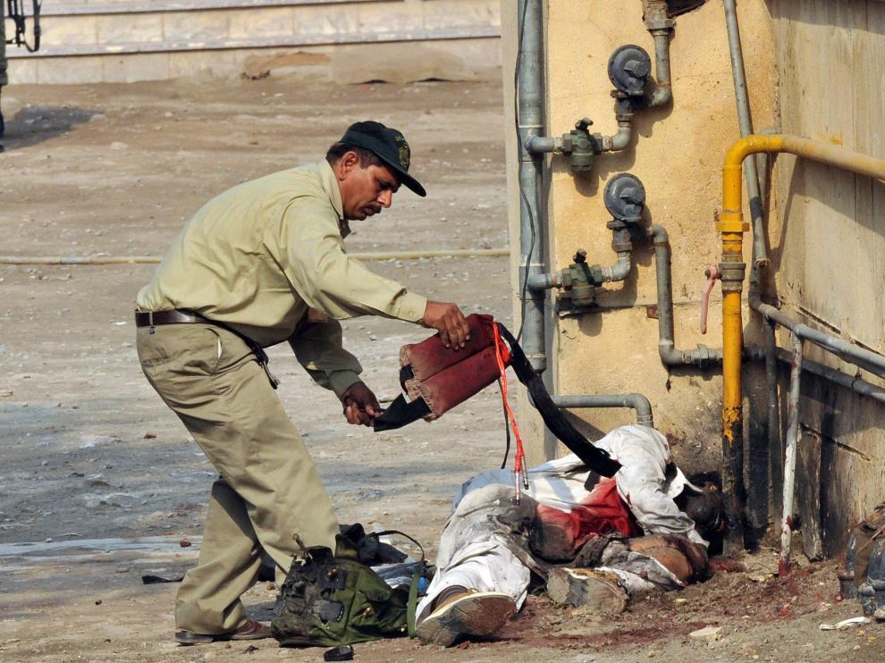 Un agente pakistaní retira el chaleco de uno de los terroristas suicidas