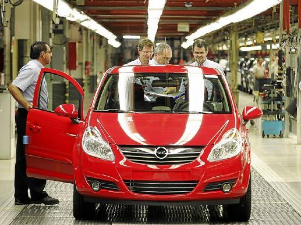 Operarios de la fábrica de Opel en Figueruelas comprueban uno de los vehículos de cadena.