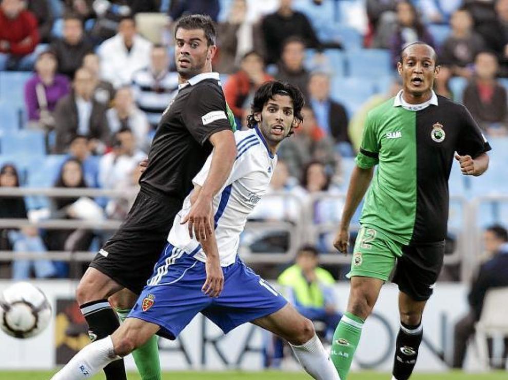 Ángel Lafita pelea un balón en el área entre los centrales del Racing, Torrejón y Morris.
