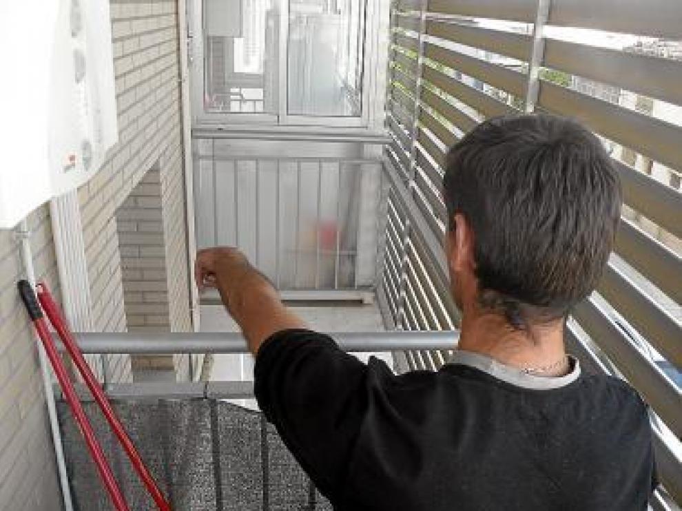 Uno de los vecinos señala la ventana desde la que saltaron.