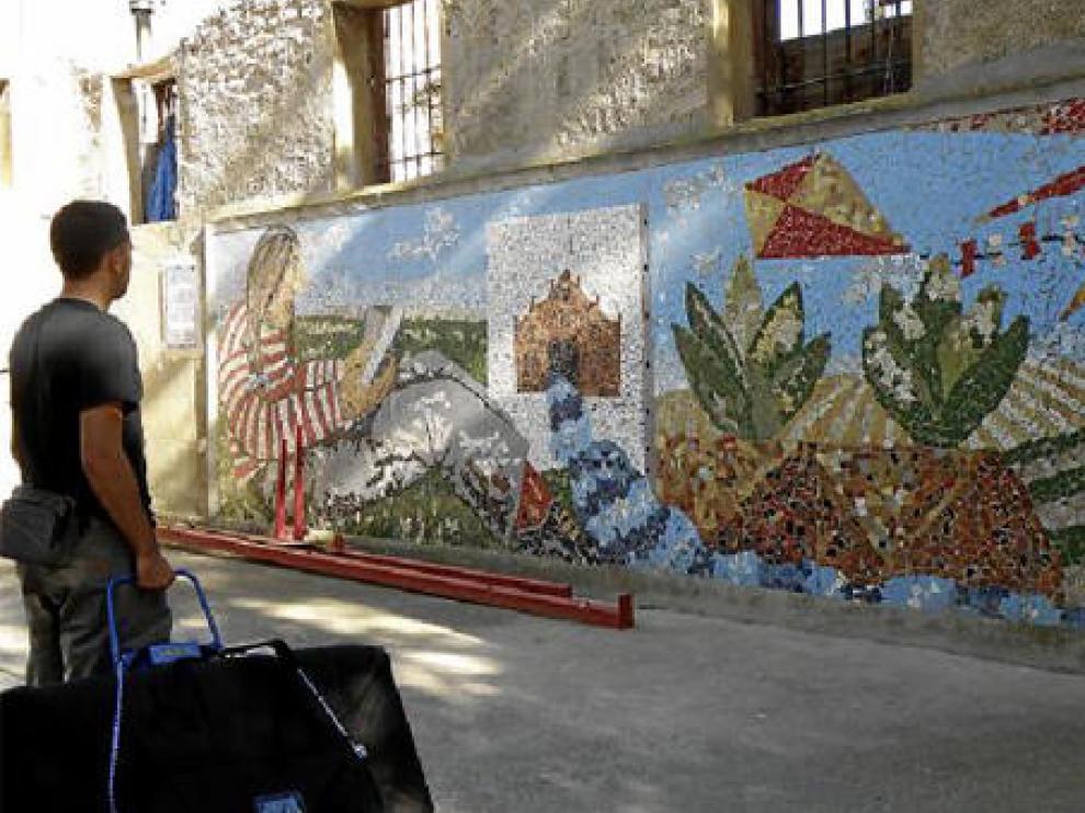Un vecino contempla el mural de Ignacio Fortún, situado en un edificio abandonado.