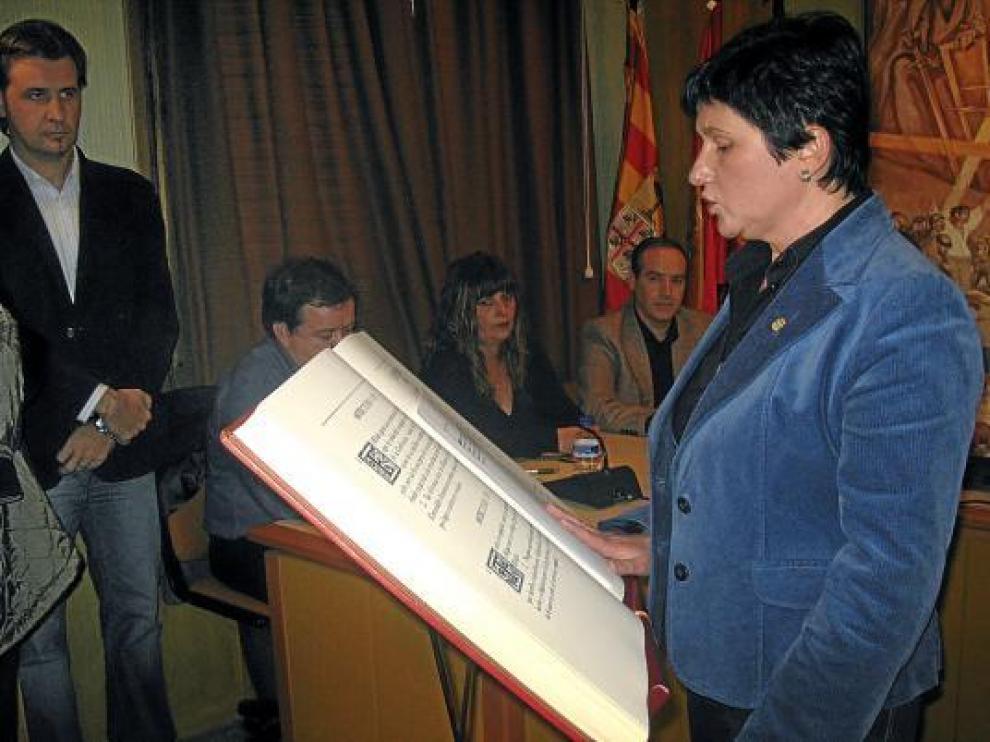 La socialista Vicente jurando su cargo como alcaldesa de Alcorisa ante la mirada de Burriel, al fondo.