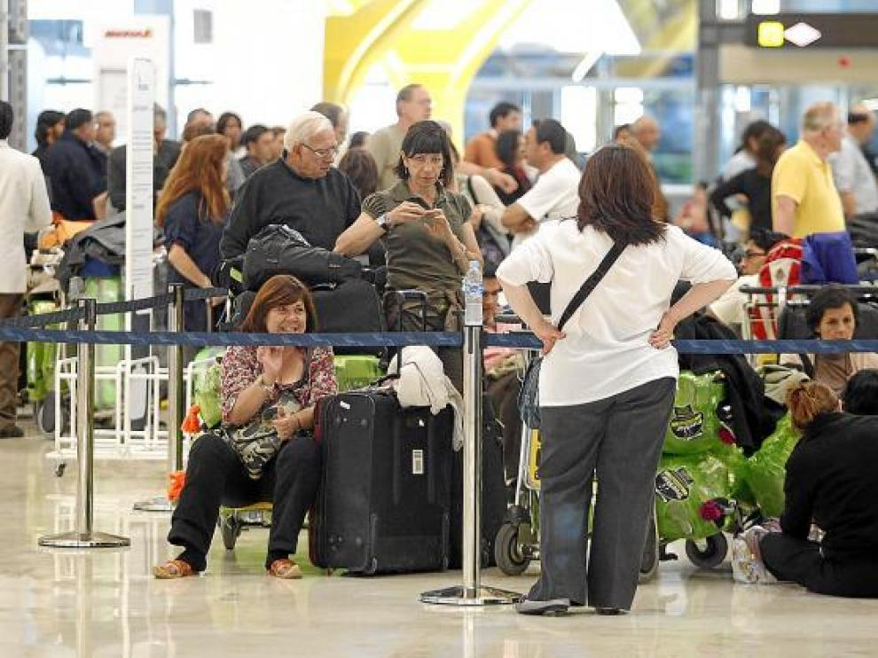 Varios pasajeros esperan conocer su vuelo, ayer en la T-4 del aeropuerto de Barajas.