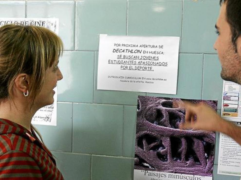 Dos estudiantes miran el cartel de Decathlon en la facultad de C.C. Humanas y de la Educación.