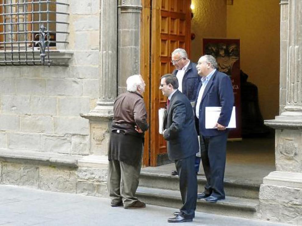 Un vecino saluda a Enrique Villarroya, José María Abarca y Juan David Vila a la salida de la comisión.