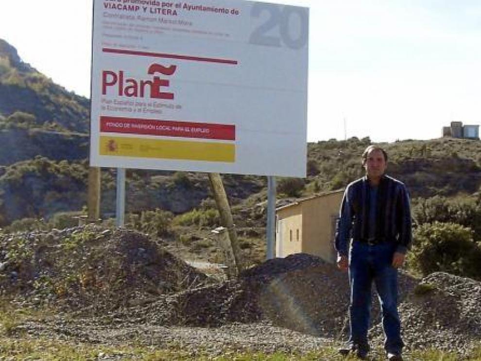 Alfredo Pociello, alcalde de Viacamp y Litera, con el cartel del Plan E, situado a la entrada del pueblo.