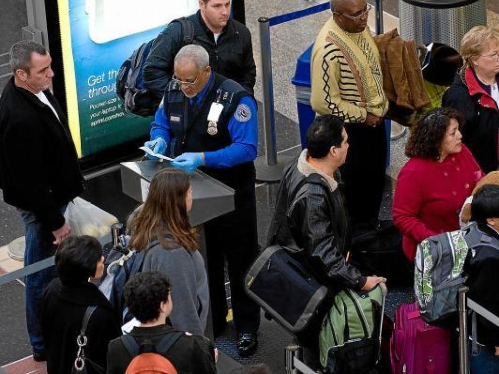Un agente identifica a los pasajeros, ayer, en el aeropuerto Ronald Reagan de Washington.
