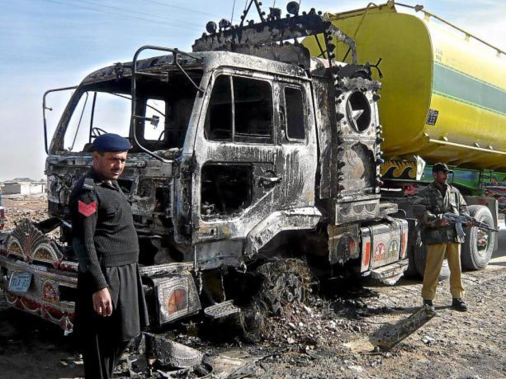 Oficiales paquistaníes, junto a un camión cisterna destinado a las fuerzas de la OTAN en Afganistán después de que fuera atacado ayer