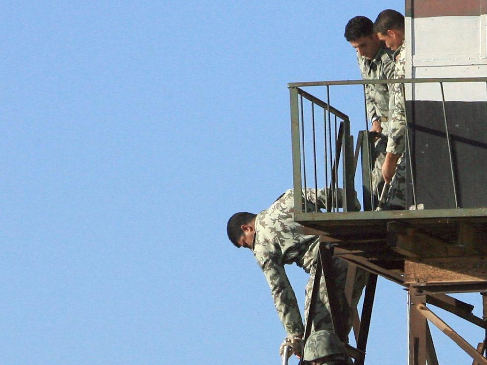 Compañeros del guardia muerto bajan su cadáver desde la torre de control fronteriza