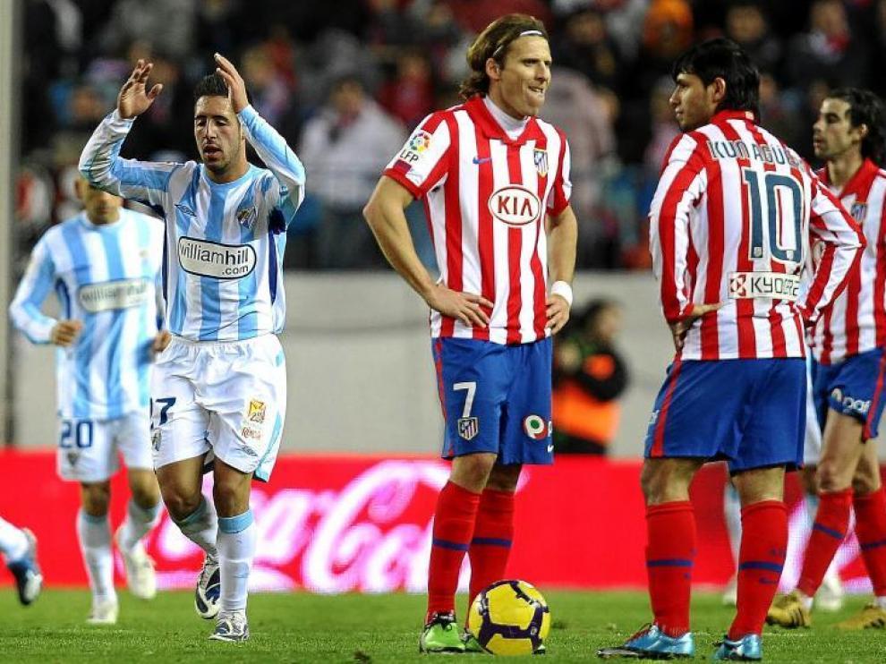 Diego Forlán y el 'Kun' Agüero, resignados, se disponen a sacar de centro tras el 0-2 del Málaga.