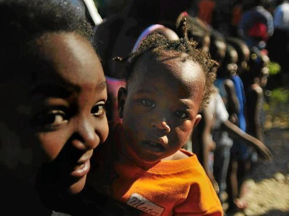 Una mujer sostiene en brazos a un niño en un refugio, ayer en Puerto Príncipe
