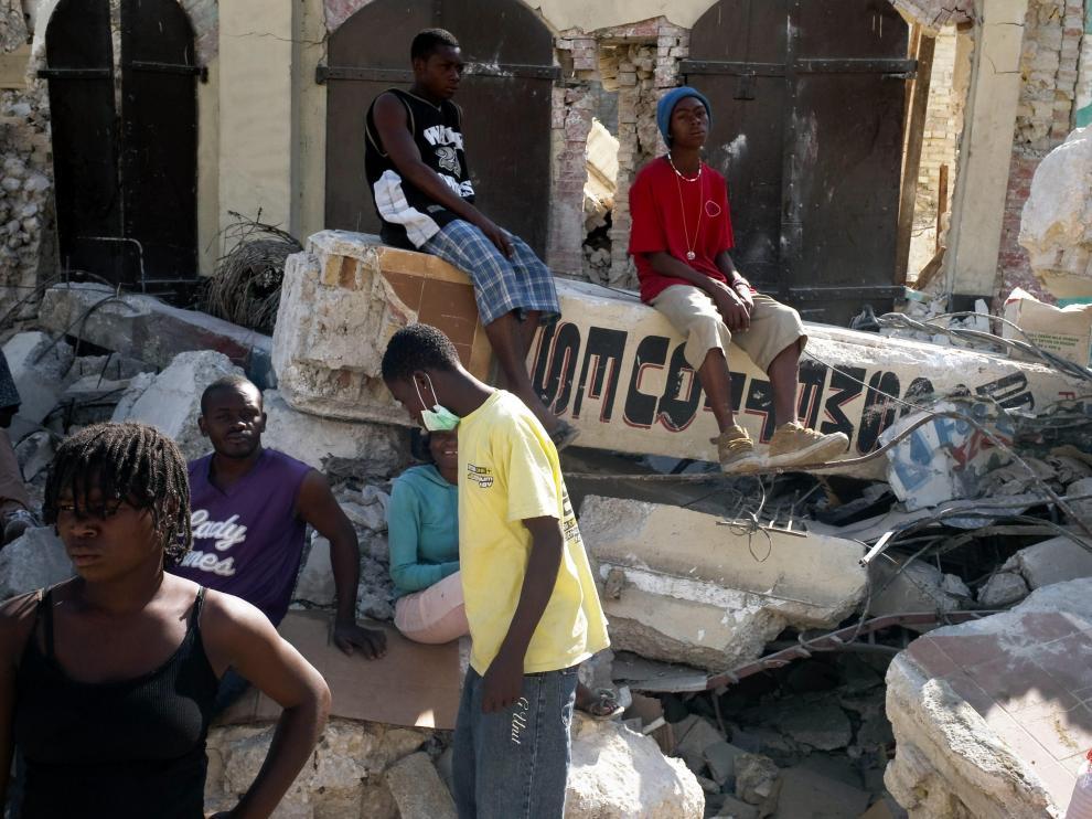 Varios ciudadanos haitianos junto a los escombros de un edificio derruído por el terremoto