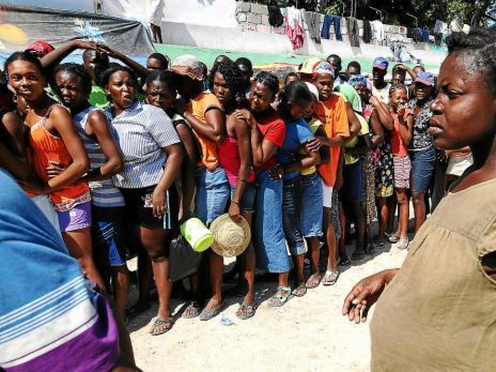 Una embarazada, frente a las mujeres que esperan la distribución de agua, en Puerto Príncipe