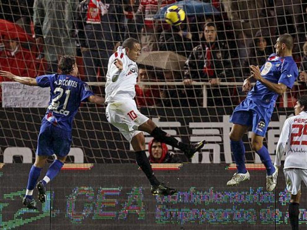 El sevillista Luis Fabiano envía el balón a la red, ante la presencia de Cortés y Díaz.