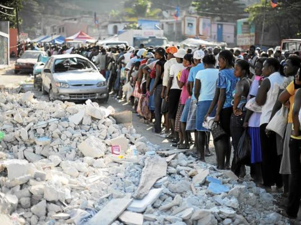 Los haitianos hacen fila para recibir alimentos junto a unos escombros, ayer en Puerto Príncipe