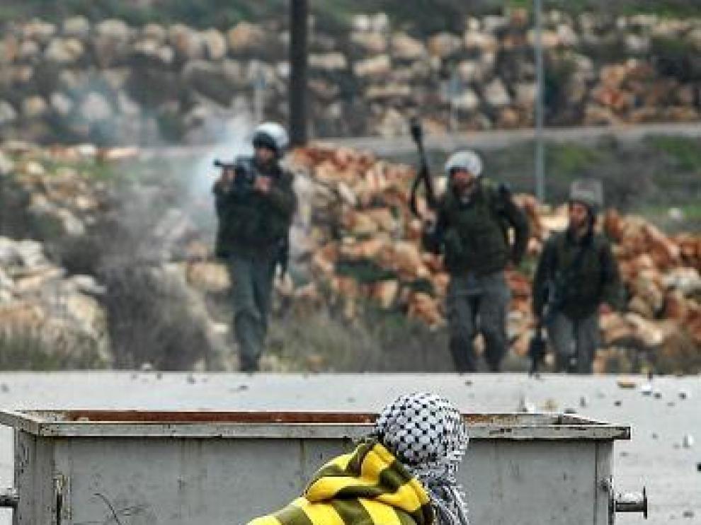 Un palestino se prepara para tirar piedras a la Policía israelí