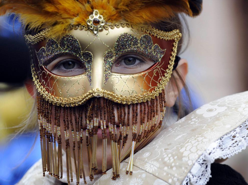 Una joven, ataviada con una delicada máscara de carnaval veneciana, en la plaza de San Marcos.