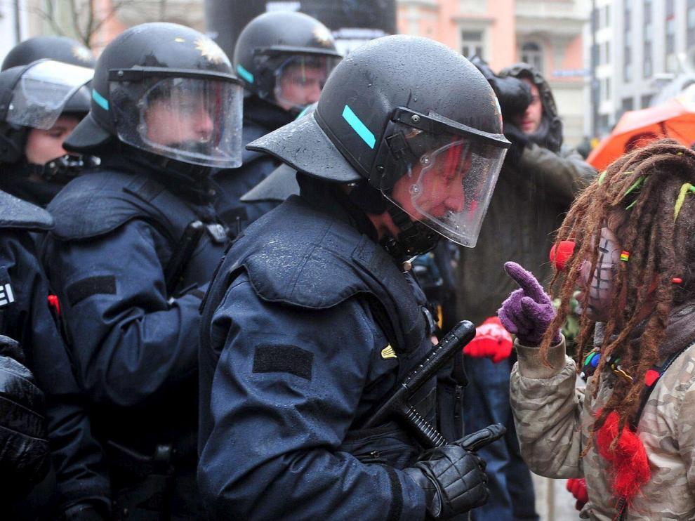 Una manifestante vestida de payasa regaña a un policía en una protesta contra la Conferencia de Seguridad, ayer en Múnich.