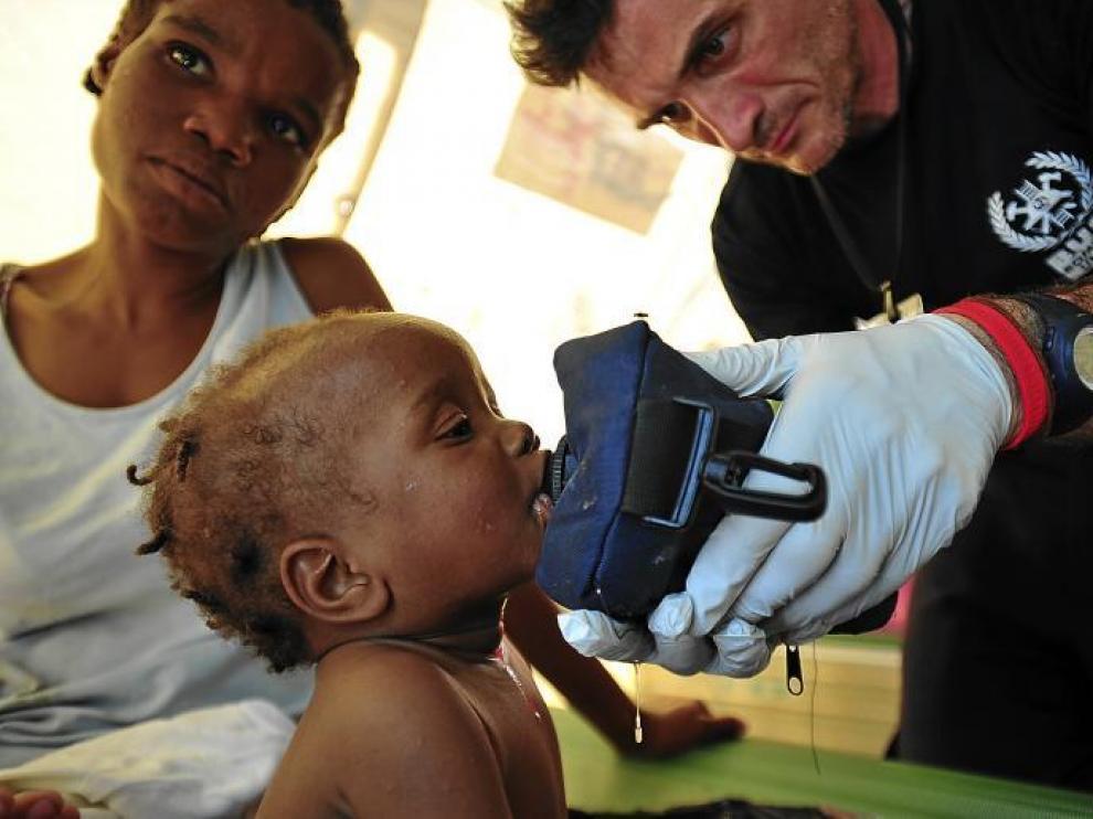 El bombero aragonés Kike Mur da de beber a un pequeño haitiano, en Puerto Príncipe (Haití)