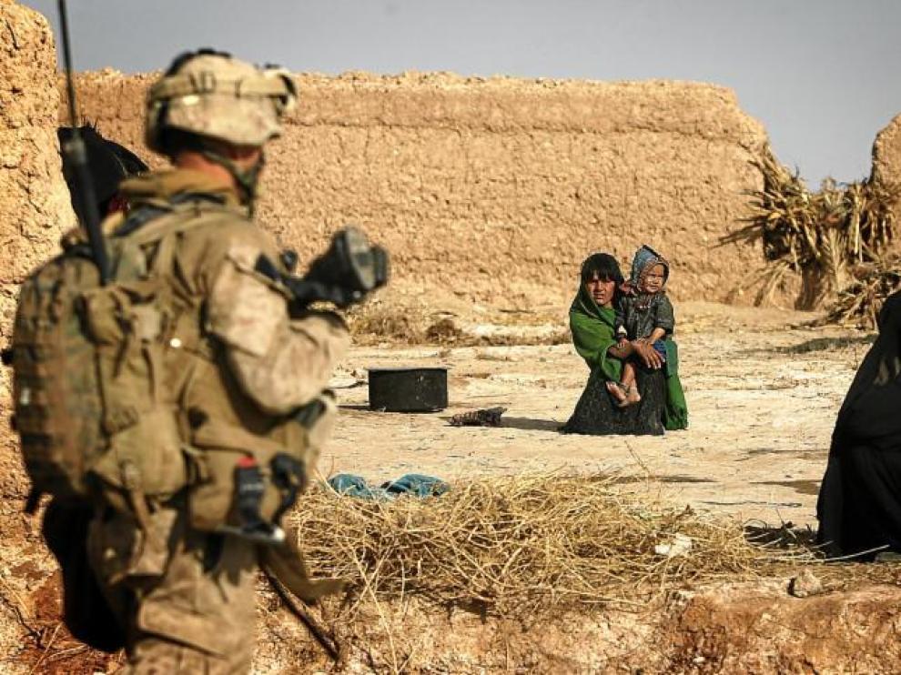 Un soldado estadounidense observa a dos mujeres afganas, una con un niño en Afganistán