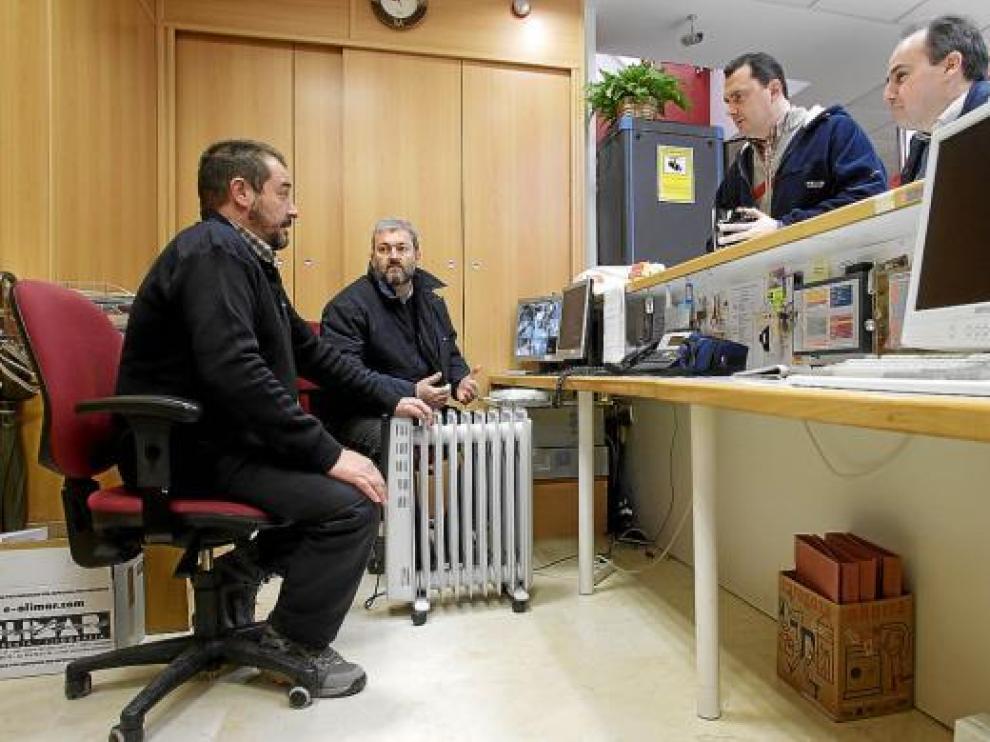 Dos oficiales se calientan con un calefactor en la recepción del centro cívico.
