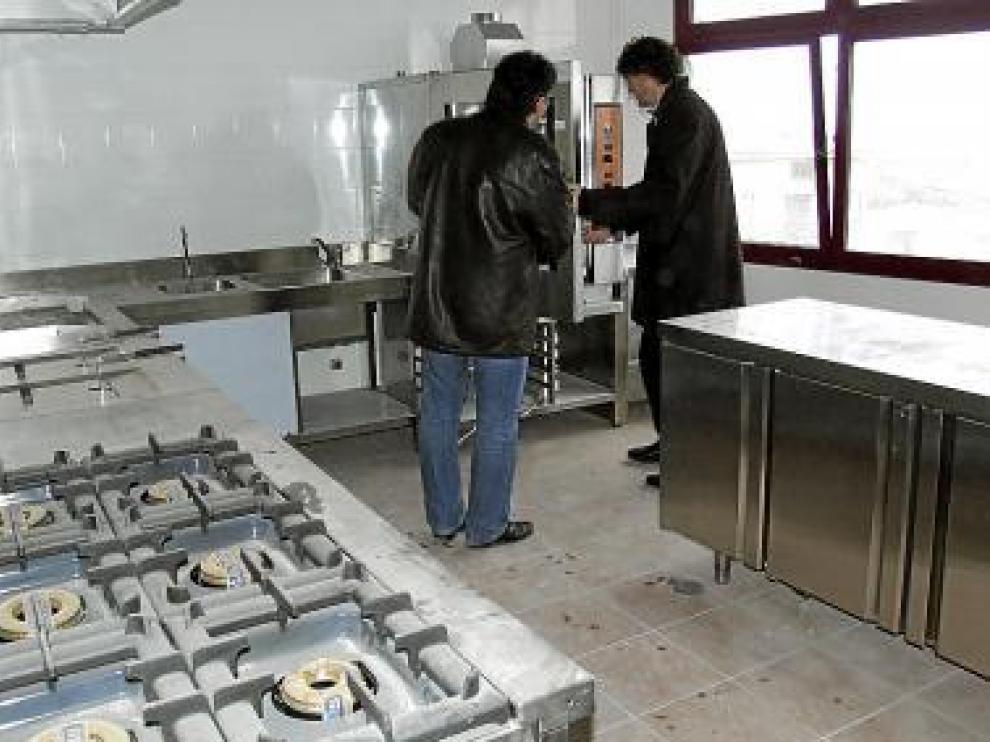 El alcalde (dcha.) y el secretario, en las cocinas del local.