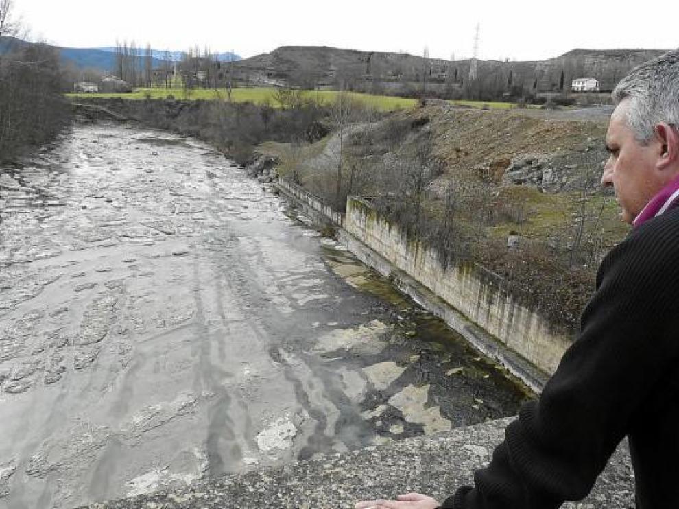 Miguel Ángel Sádaba observa el río Aragón a su paso por Jaca, que ayer llevaba más de agua.