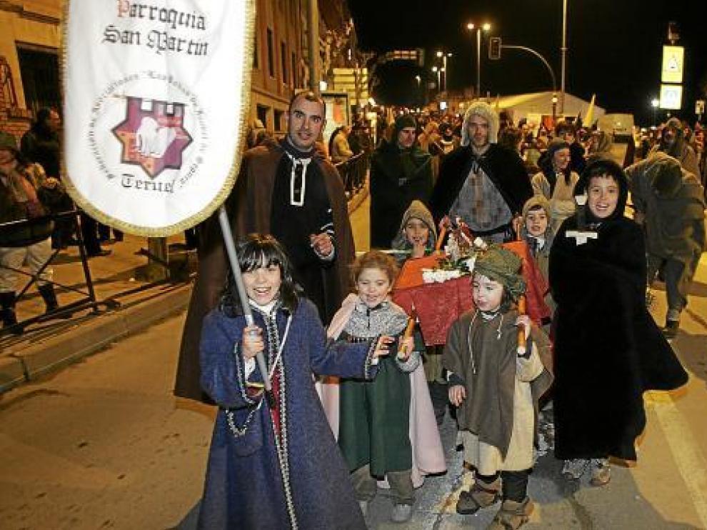Un grupo de niños porta el estandarte de la parroquía medieval de San Martín