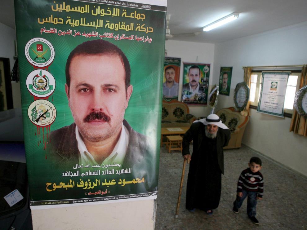 El padre y el nieto de Al Mabhuh pasan bajo un póster con su imagen en su casa de Jabalia, en el norte de la franja de Gaza, ayer