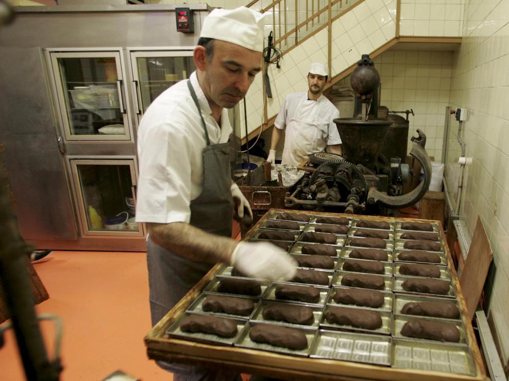 Algunos de los maestros pasteleros trabajan el chocolate en el obrador.