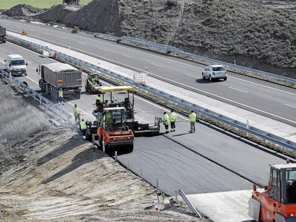 La empresa constructora reasfaltaba ayer la zona afectada por el hundimiento en sentido Huesca