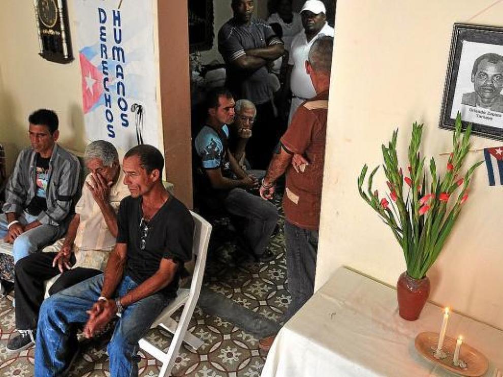 Opositores cubanos, ayer, en la casa de la líder de las Damas de Blanco junto a una foto de Zapata
