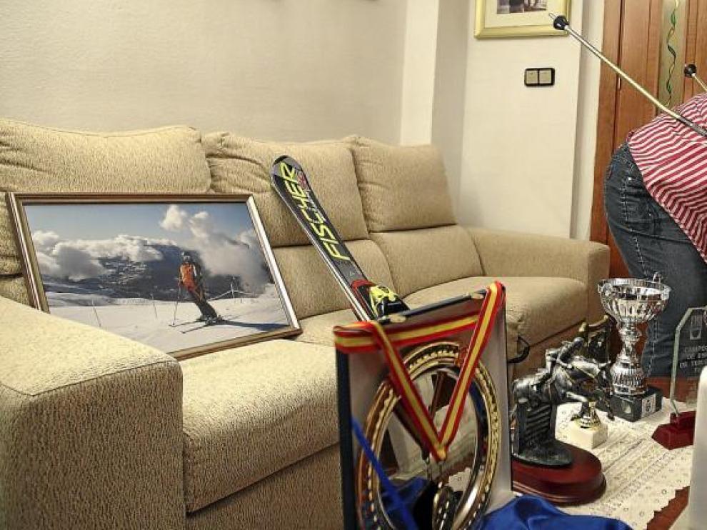 Beatriz, en el salón de su casa, con algunos de sus trofeos y parte de su equipación de esquí, de la que nunca se separa