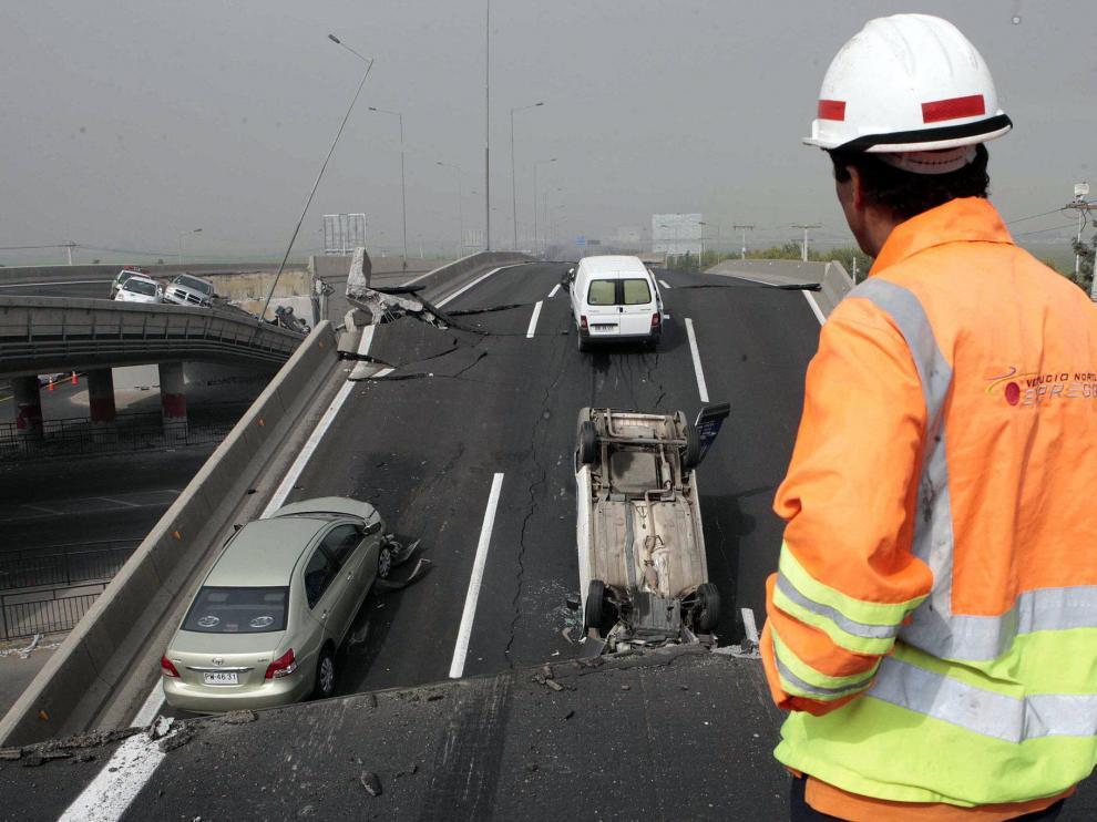 Un hombre observa los vehículos sobre un puente destruido, ayer en Santiago.