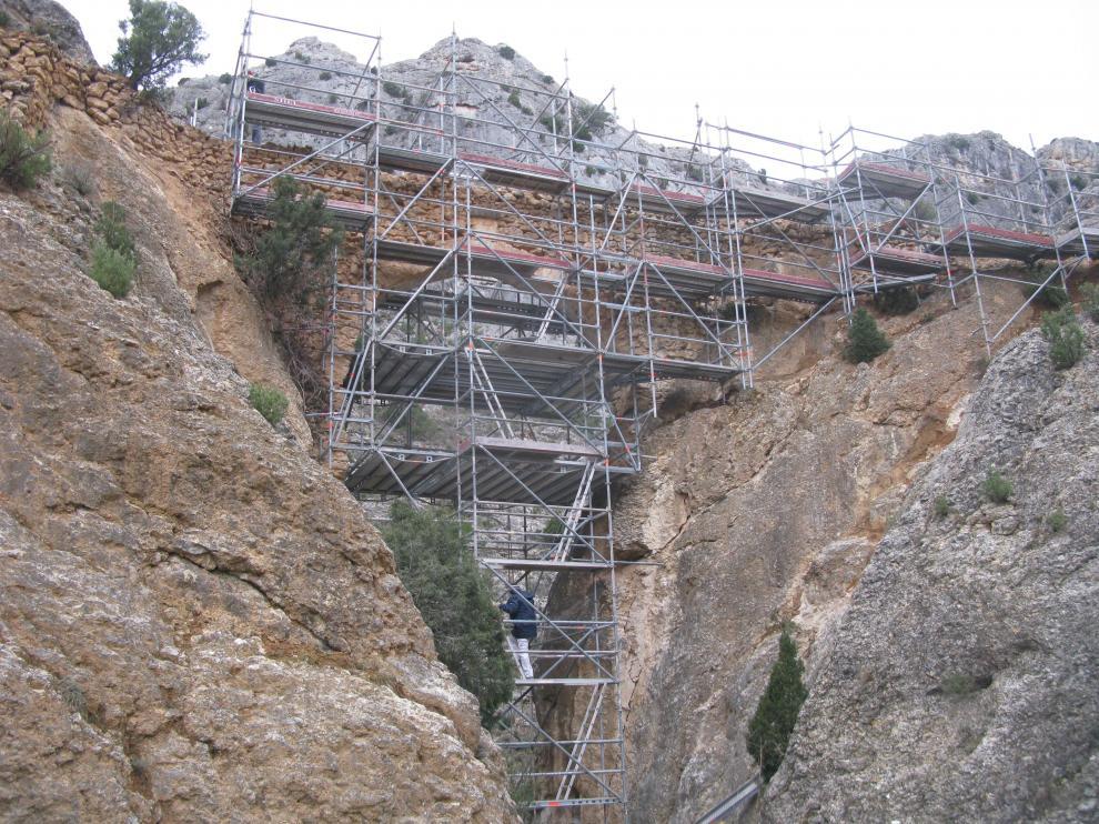 Varios obreros trabajan en la reconstrucción del histórico acueducto de Castellote.
