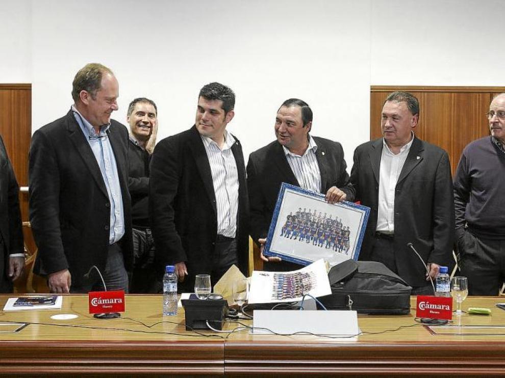 El presidente entrante, Fernando Losfablos, entrega al saliente, Armando Borraz, un cuadro de recuerdo. Al lado, Agustín Lasaosa