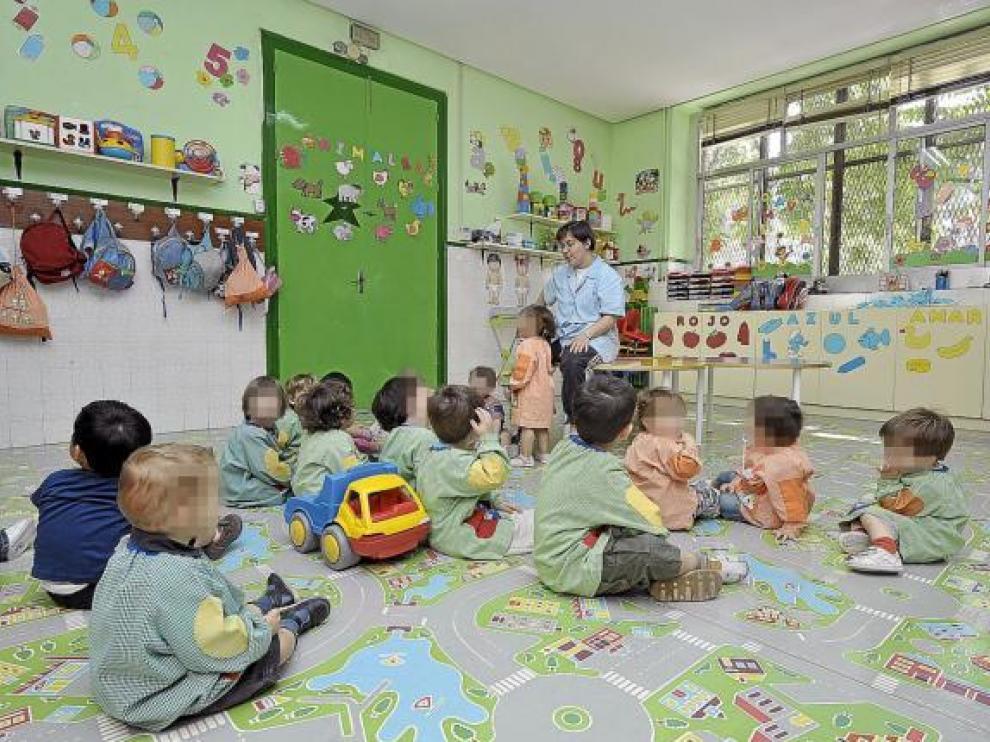 Un grupo de niños atienden a su profesora en una guardería de Zaragoza.