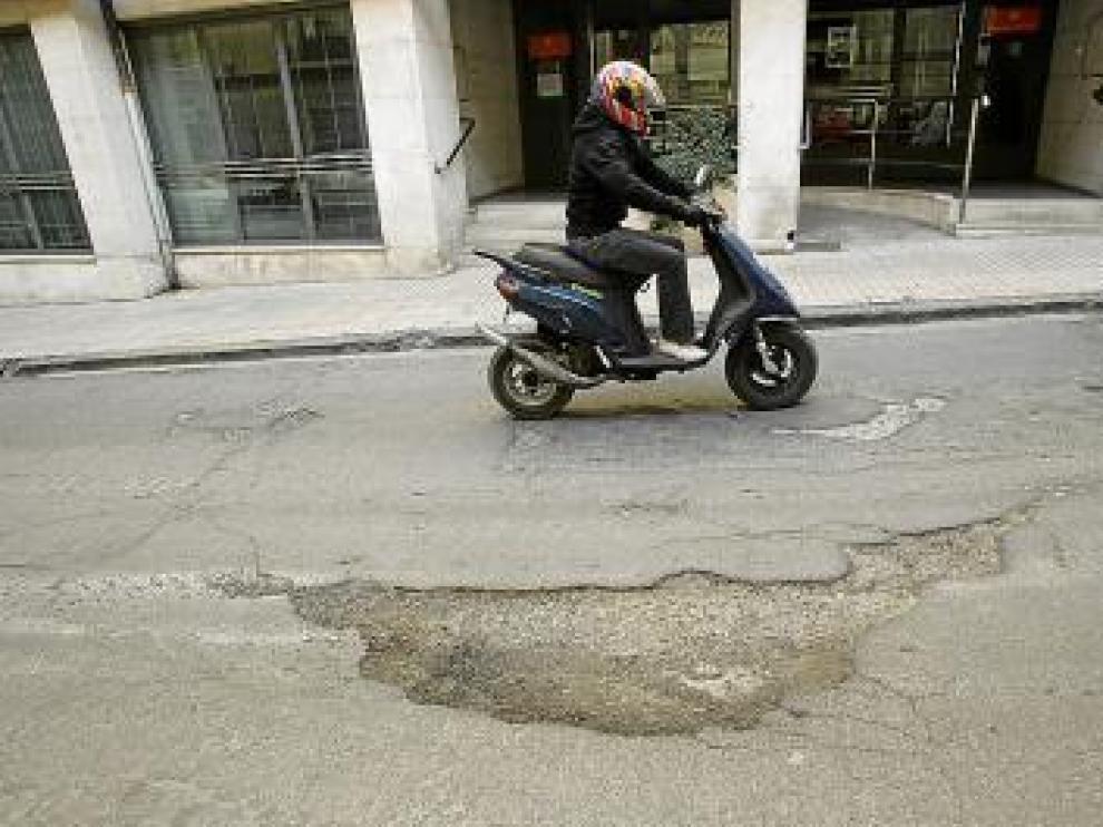 Un motorista sortea un bache en la calle Joaquín Arnau.
