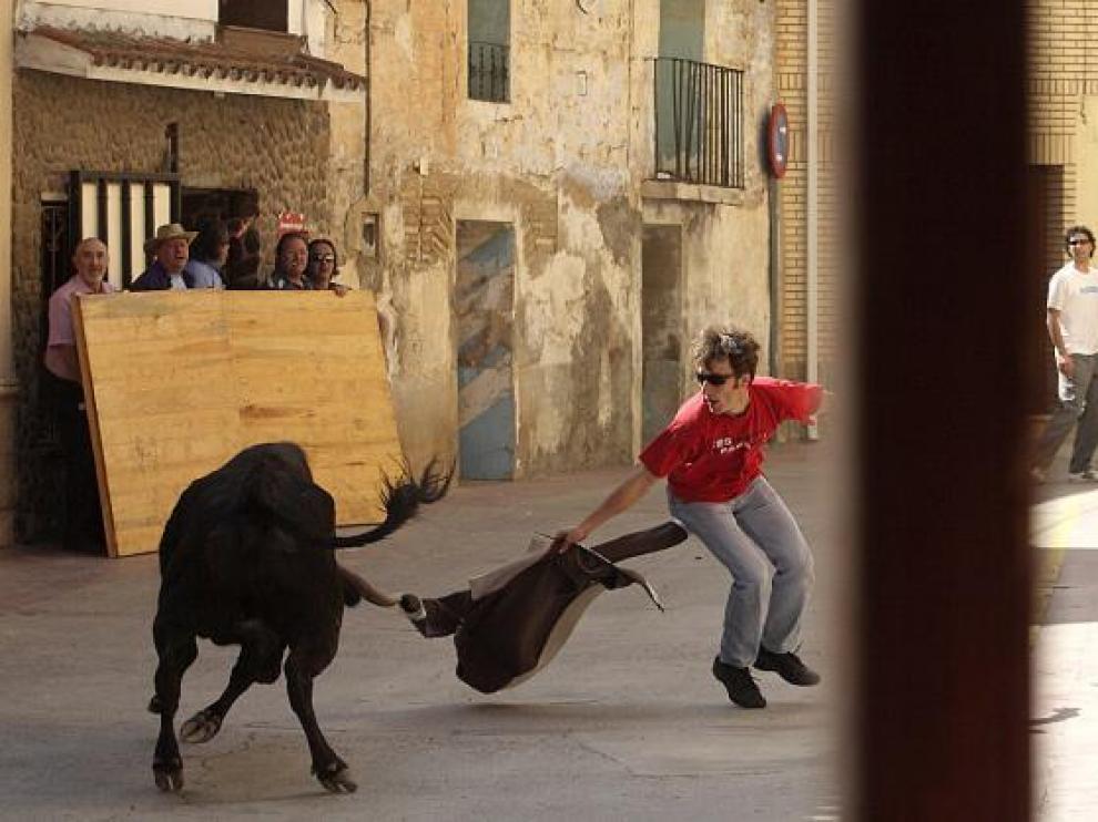 Un joven recorta una vaquilla en una calle de Pinseque.